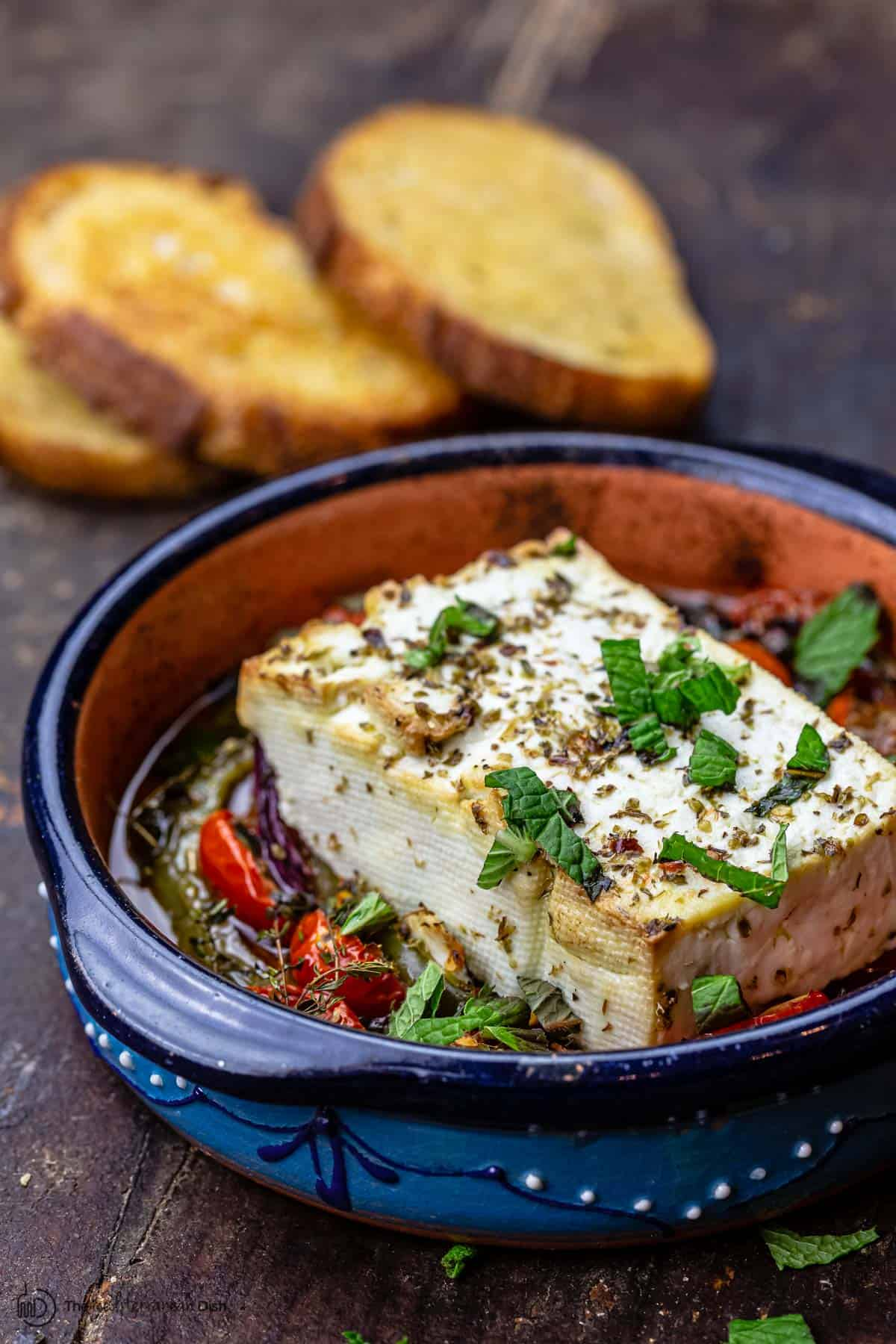 Baked feta in a serving dish with toasted bread to the side