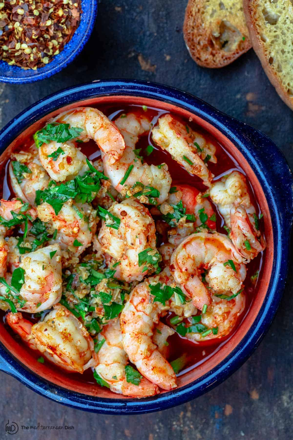 Spanish garlic shrimp with a side of bread and hot red pepper flakes