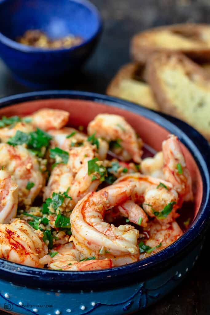 Spanish gambas al ajillo with a side of toasted bread and red pepper flakes