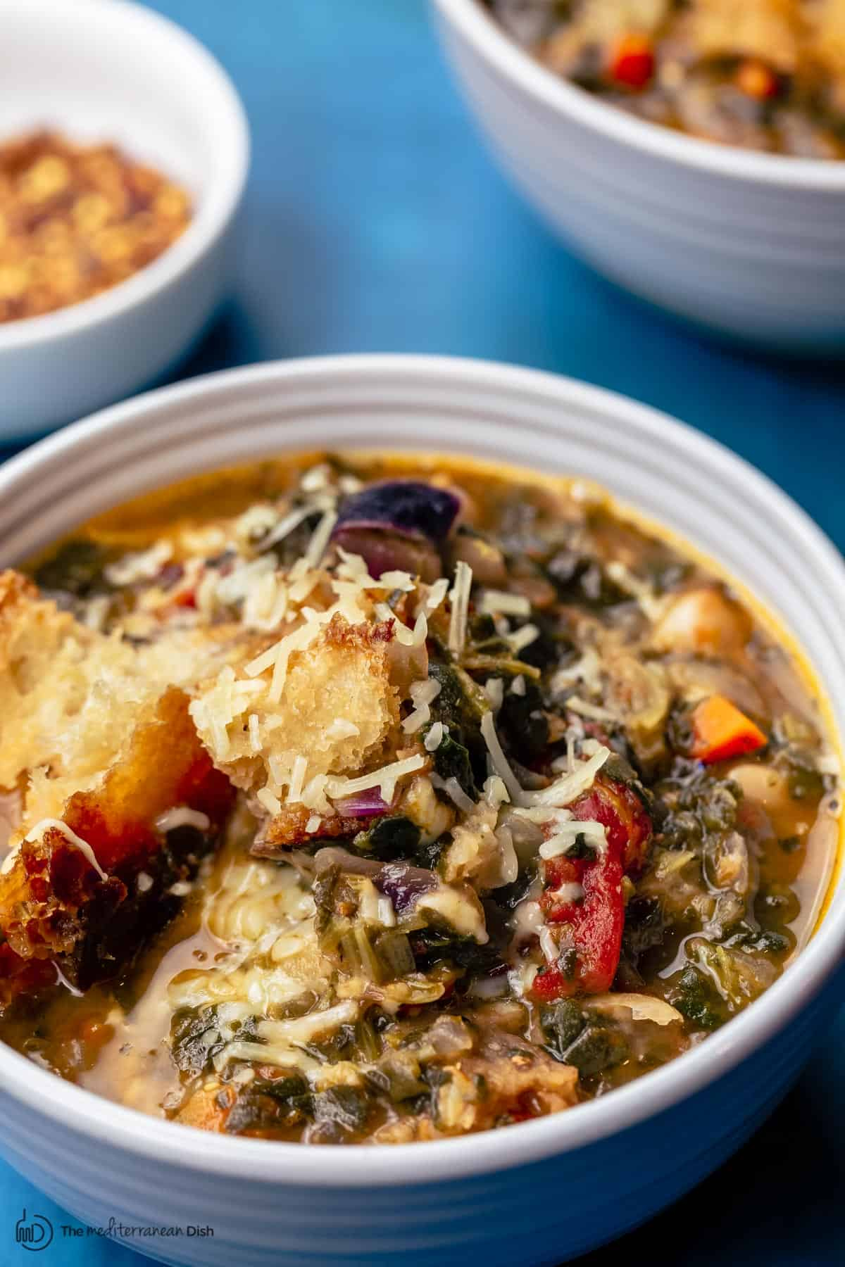 Ribollita in serving bowls with a side of crushed red pepper flakes