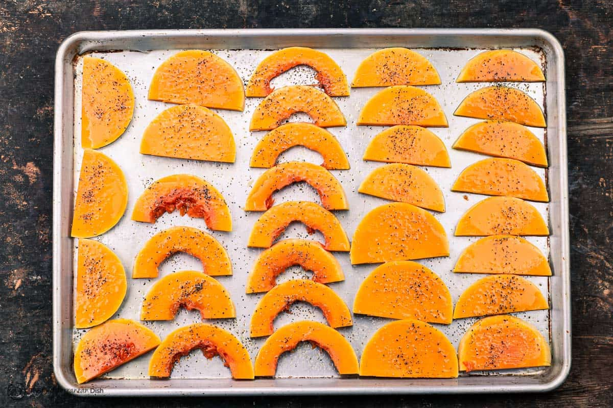 Slices of butternut squash on a baking sheet