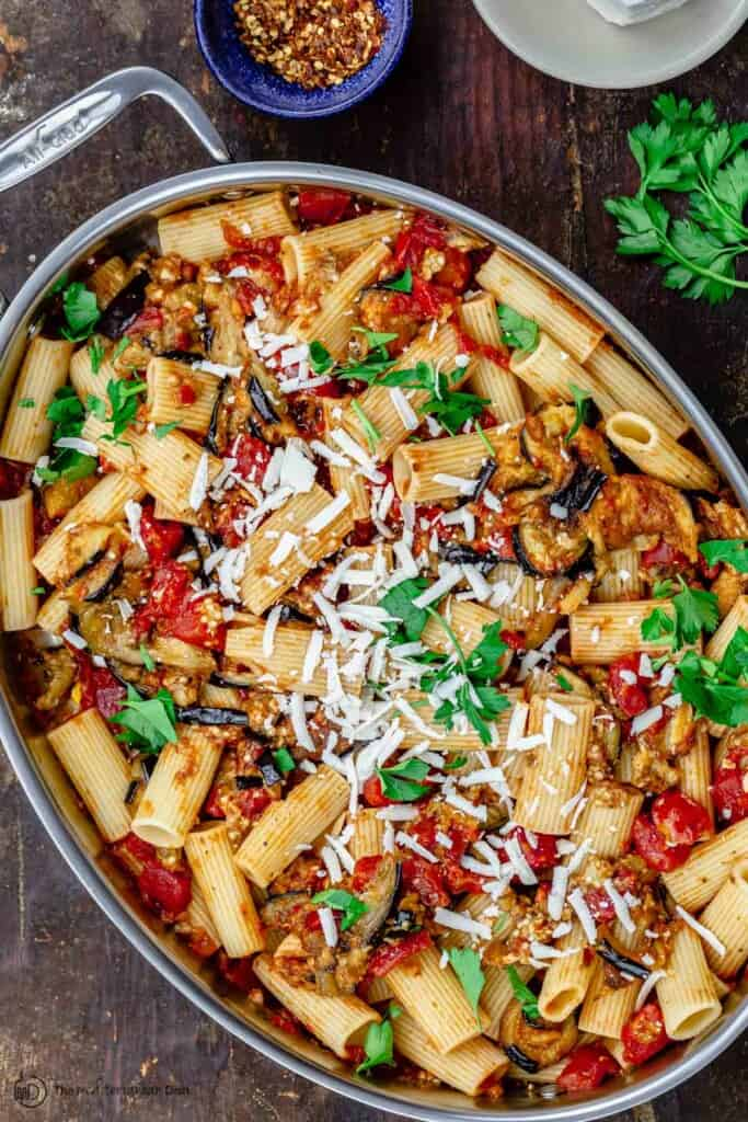 pasta alla norma in big pan with a side of crushed pepper flakes