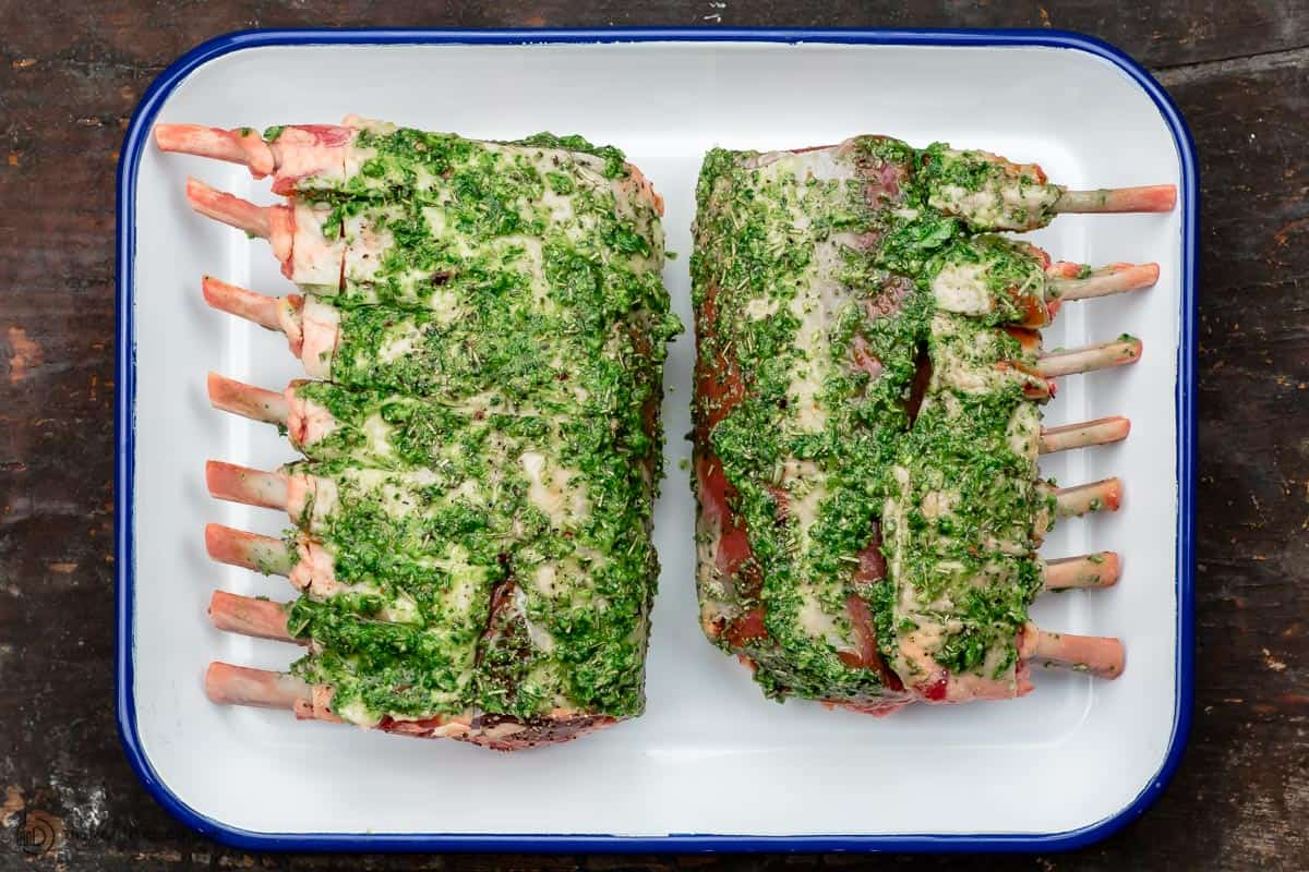 Rack of lamb with garlic and herb marinade covering it on both sides