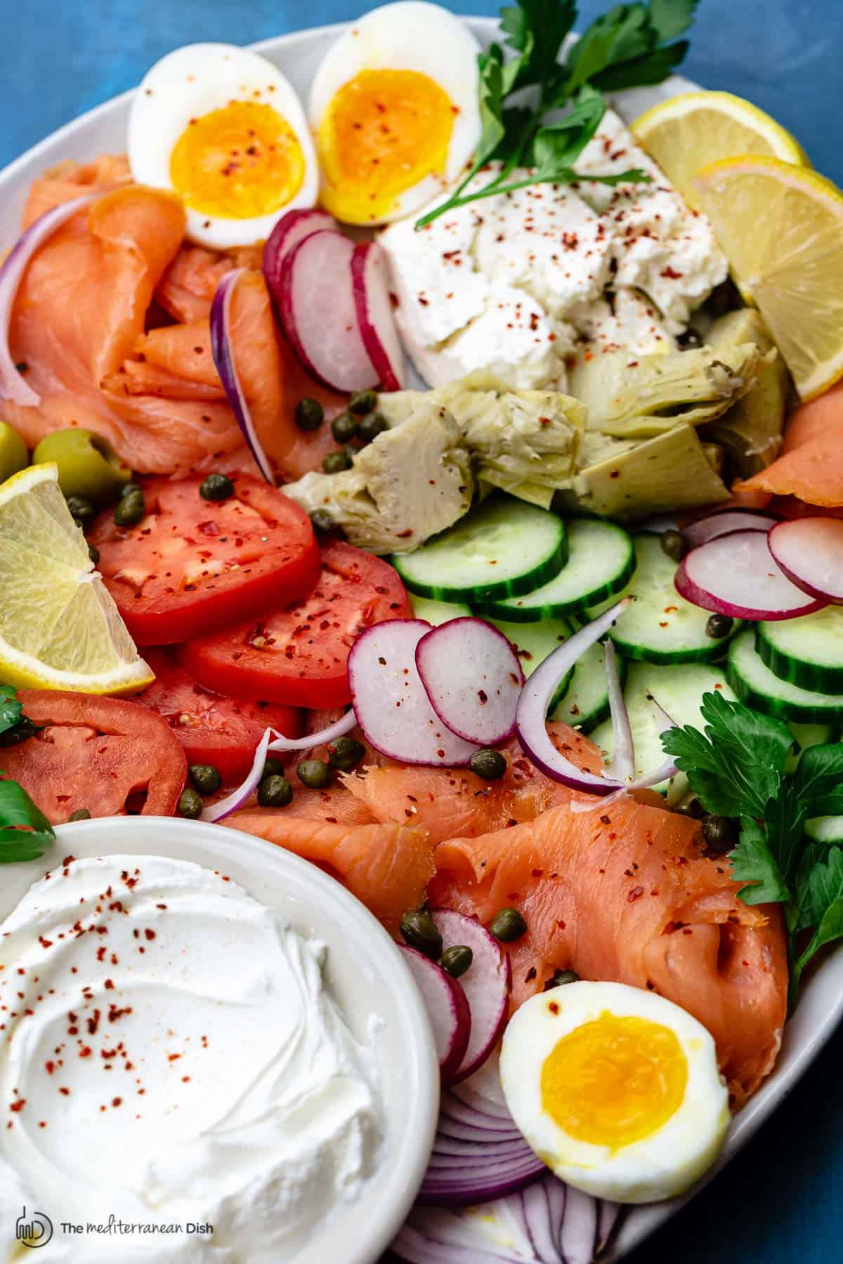 smoked salmon, fresh veggies, labneh cheese and eggs on a platter