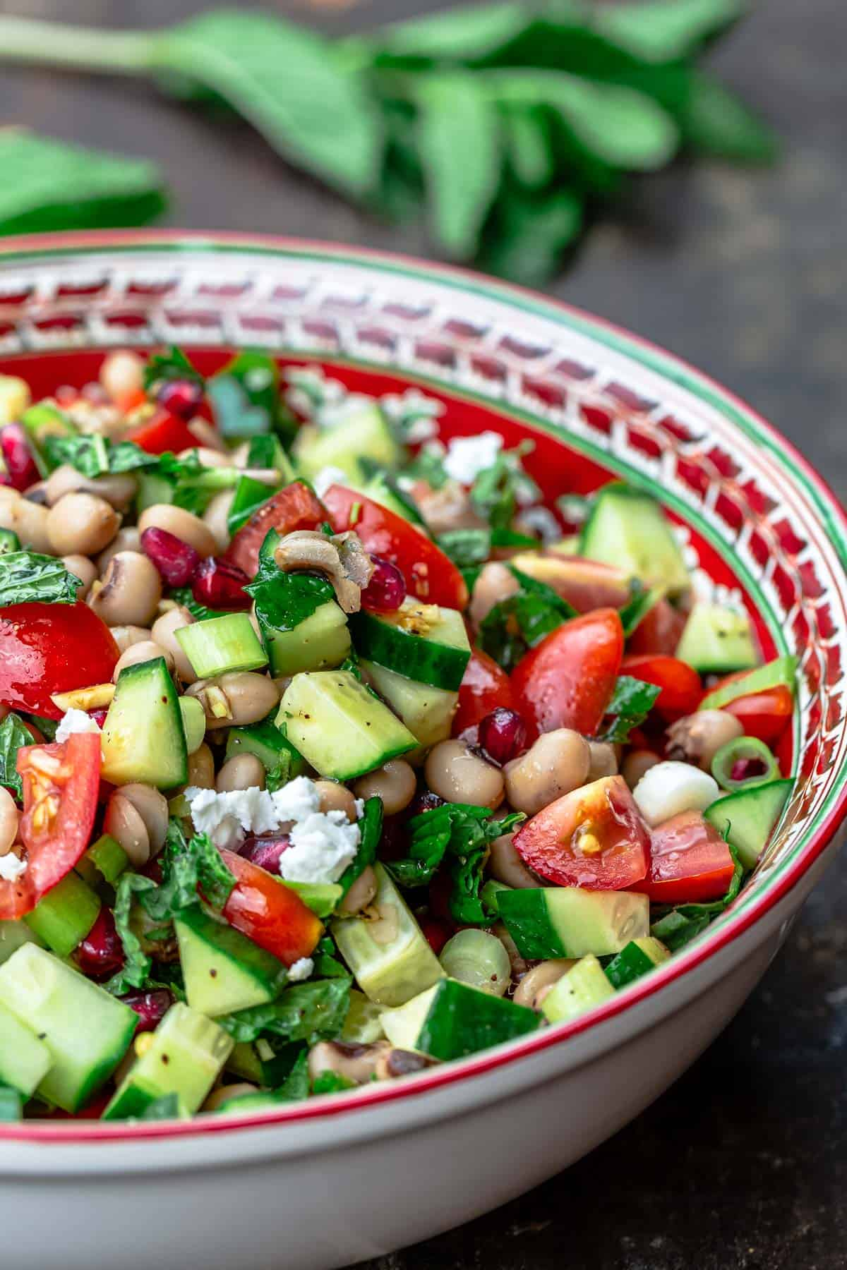 bowl of black eyed pea salad with garnish of fresh mint to the side