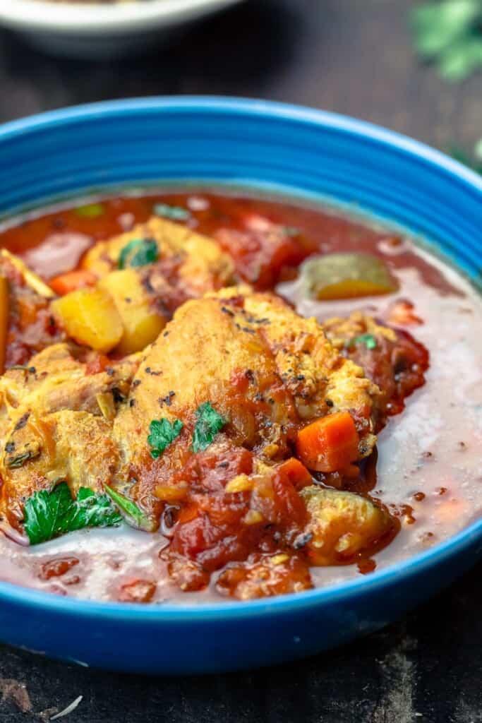Mediterranean-style chicken stew served in a blue bowl