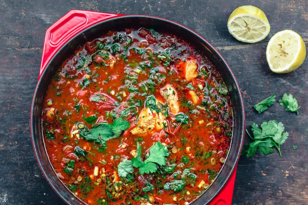 fish soup garnished with parsley and cilantro with a side of cut lemons
