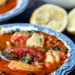 Bowls of Mediterranean Fish Soup with Lemon Wedges to the Side