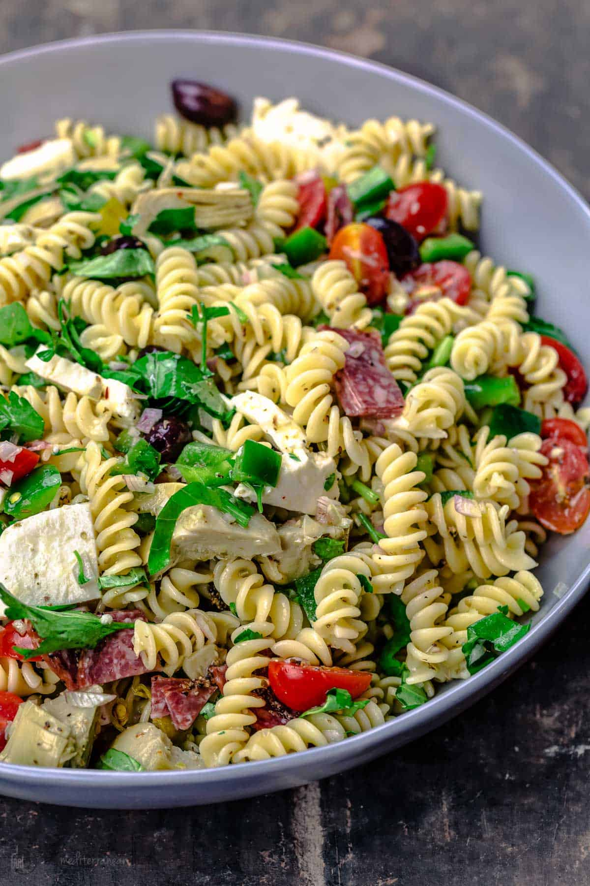 Italian pasta salad with fresh veggies, mozzarella and salami, tossed in a big bowl