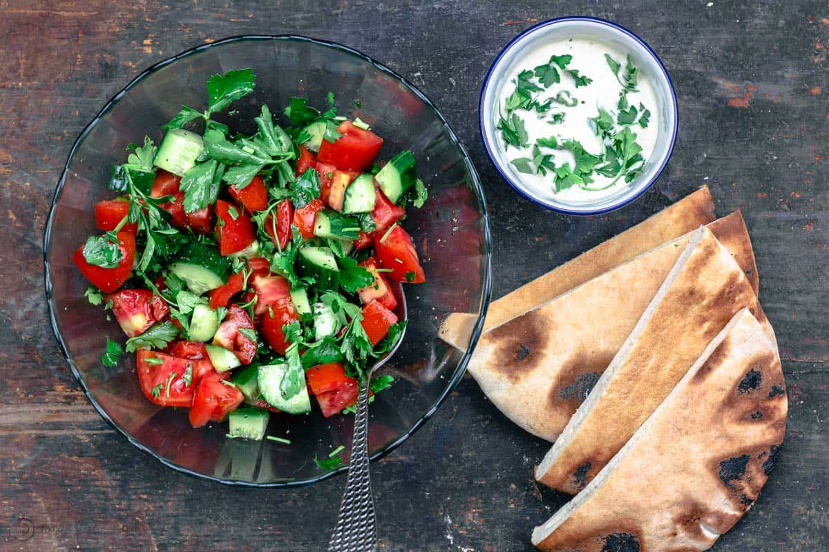 Salad mixed in bowl with a side of tahini and pita bread