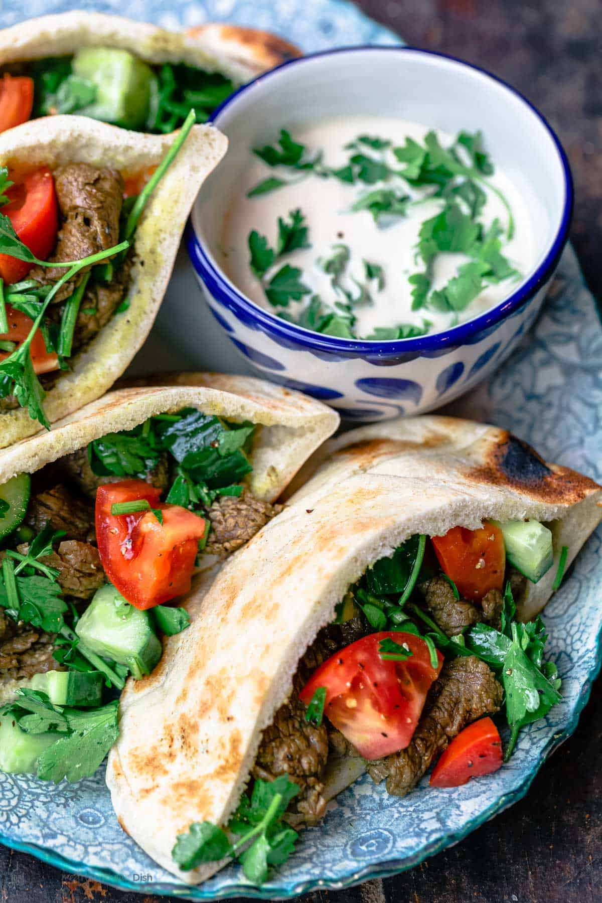 Beef shawarma pitas served on a blue plate with a side of tahini sauce