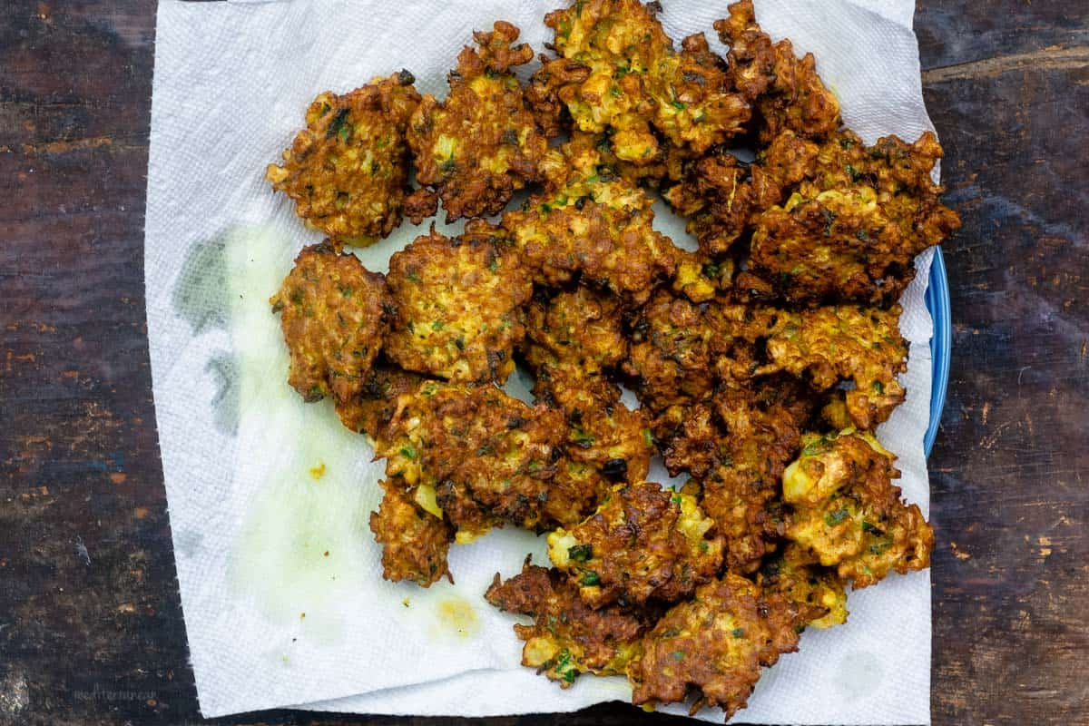 Cauliflower fritters resting on napkin to soak up excess oil