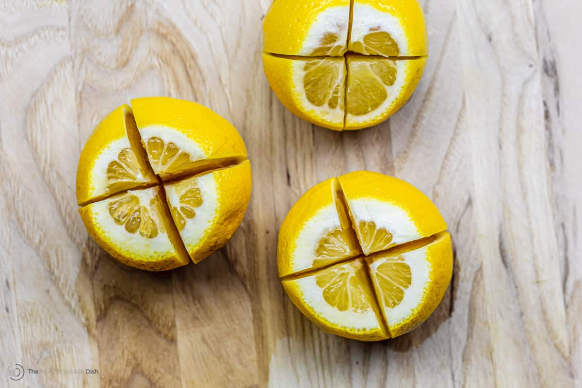 Lemons quartered on a cutting board