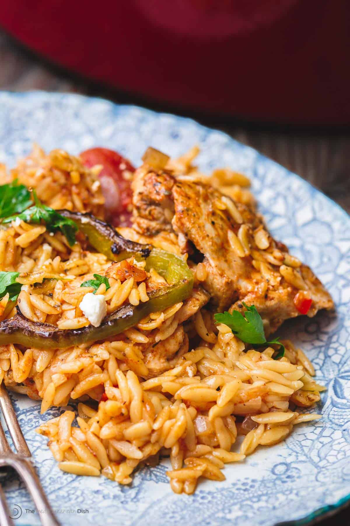 Greek chicken orzo served on a light blue plate