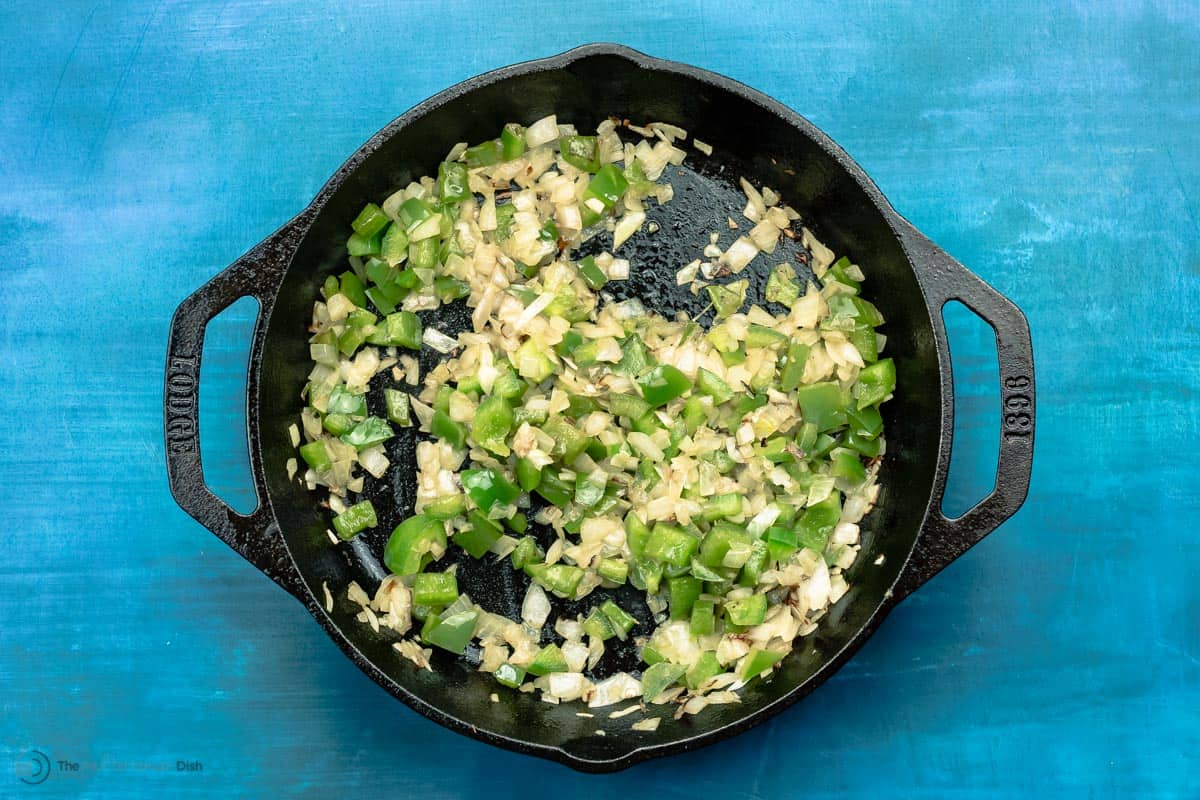 Green peppers, chopped garlic and onions sauteed in cast iron skillet