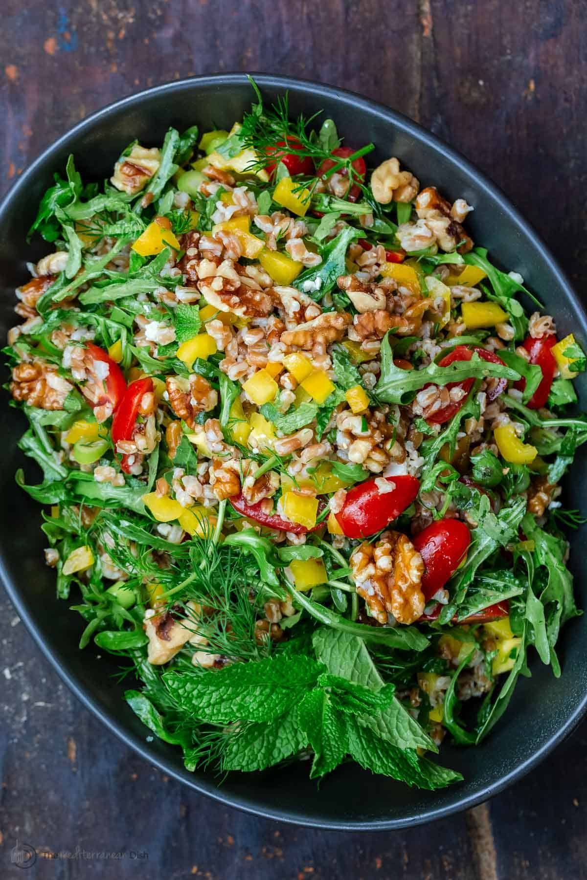 farro salad with arugula in a bowl mixed with walnuts and fresh vegetables