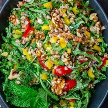 arugula and farro salad in a bowl mixed with walnuts and fresh vegetables