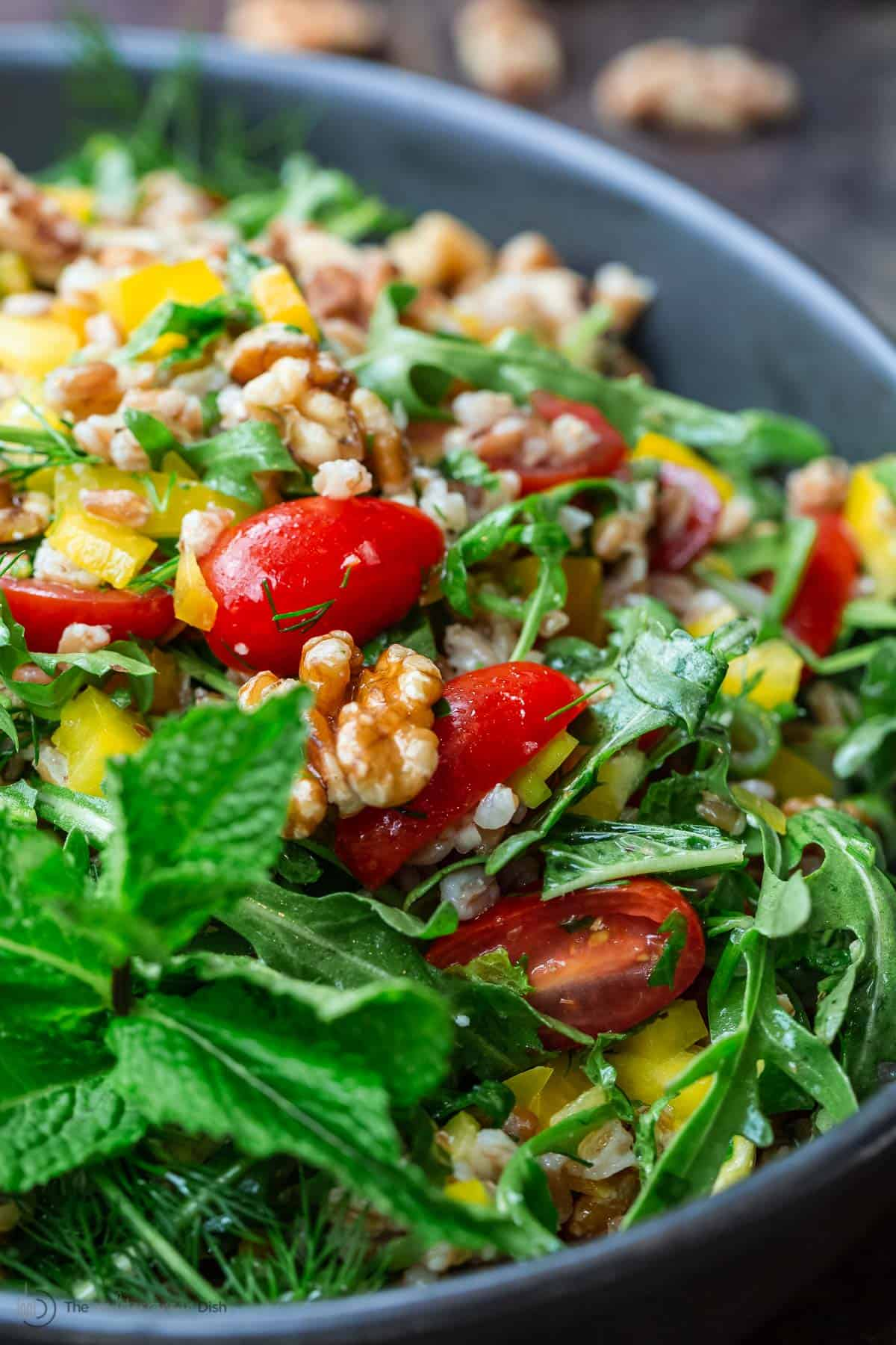 farro salad with arugula and walnuts in a bowl