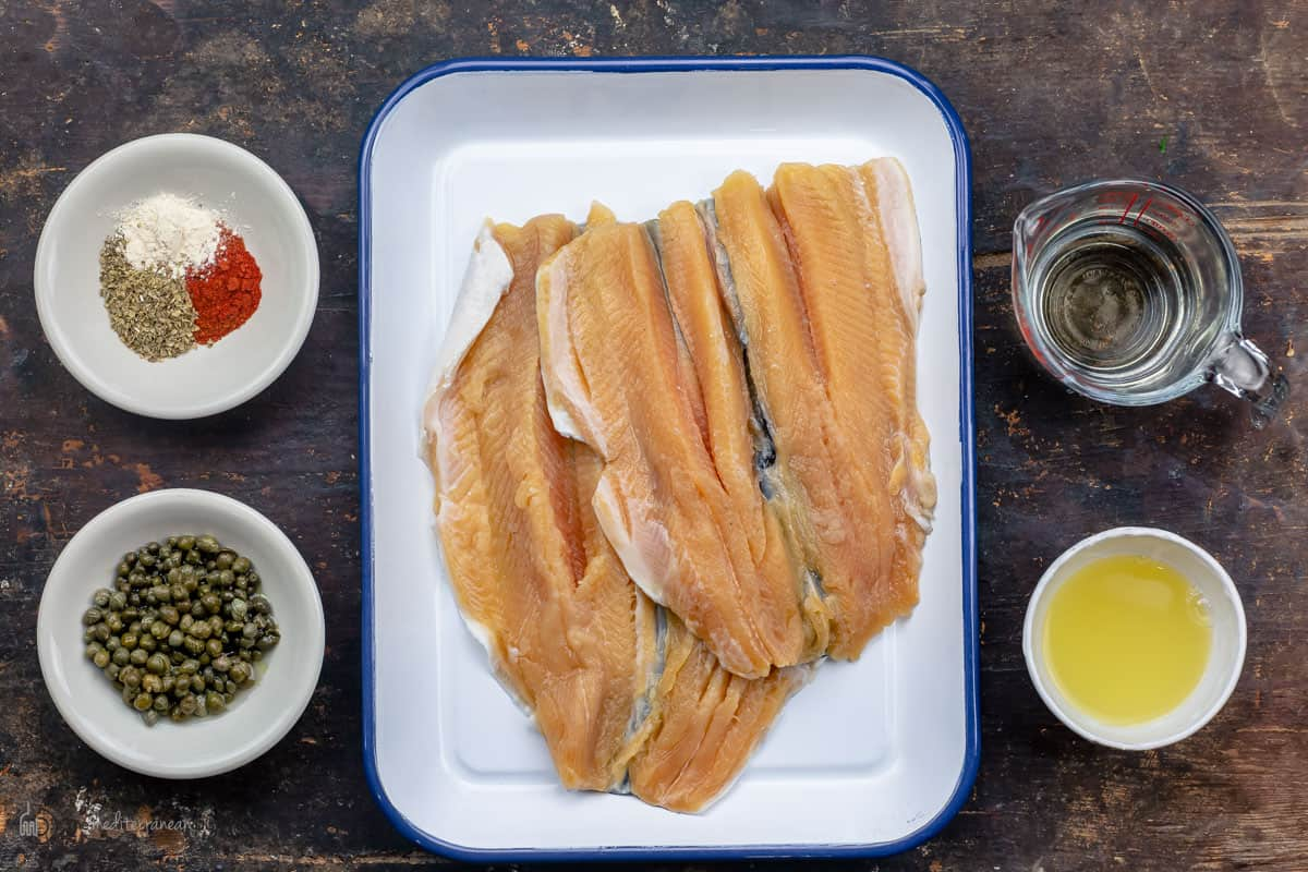 The ingredients needed to make fish piccata measured in glass dishes