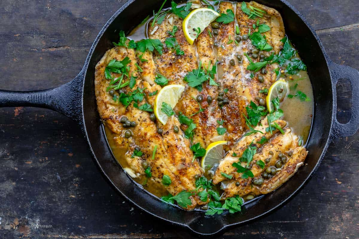 Fish piccata topped with lemon slices and parsley in a skillet