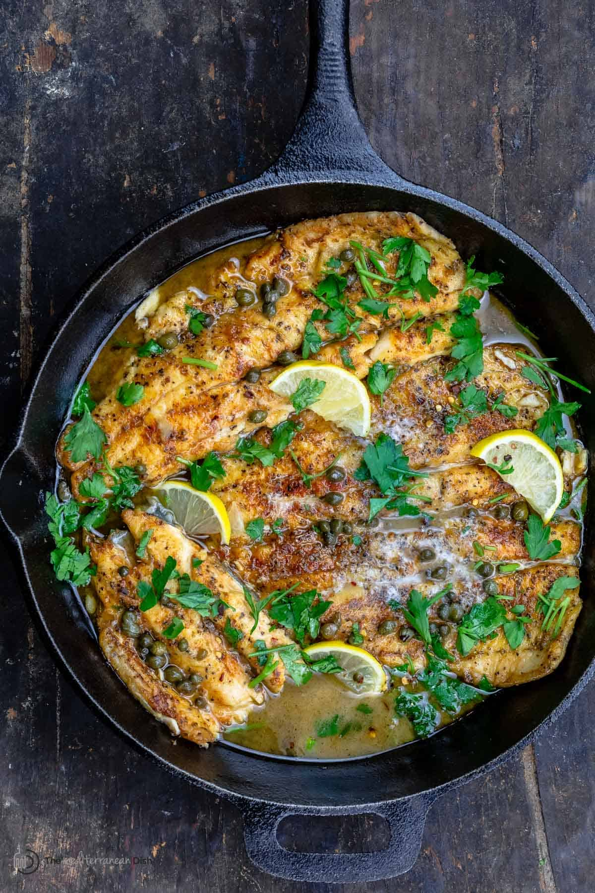 Pan-seared trout topped with a lemon piccata sauce in a cast iron skillet