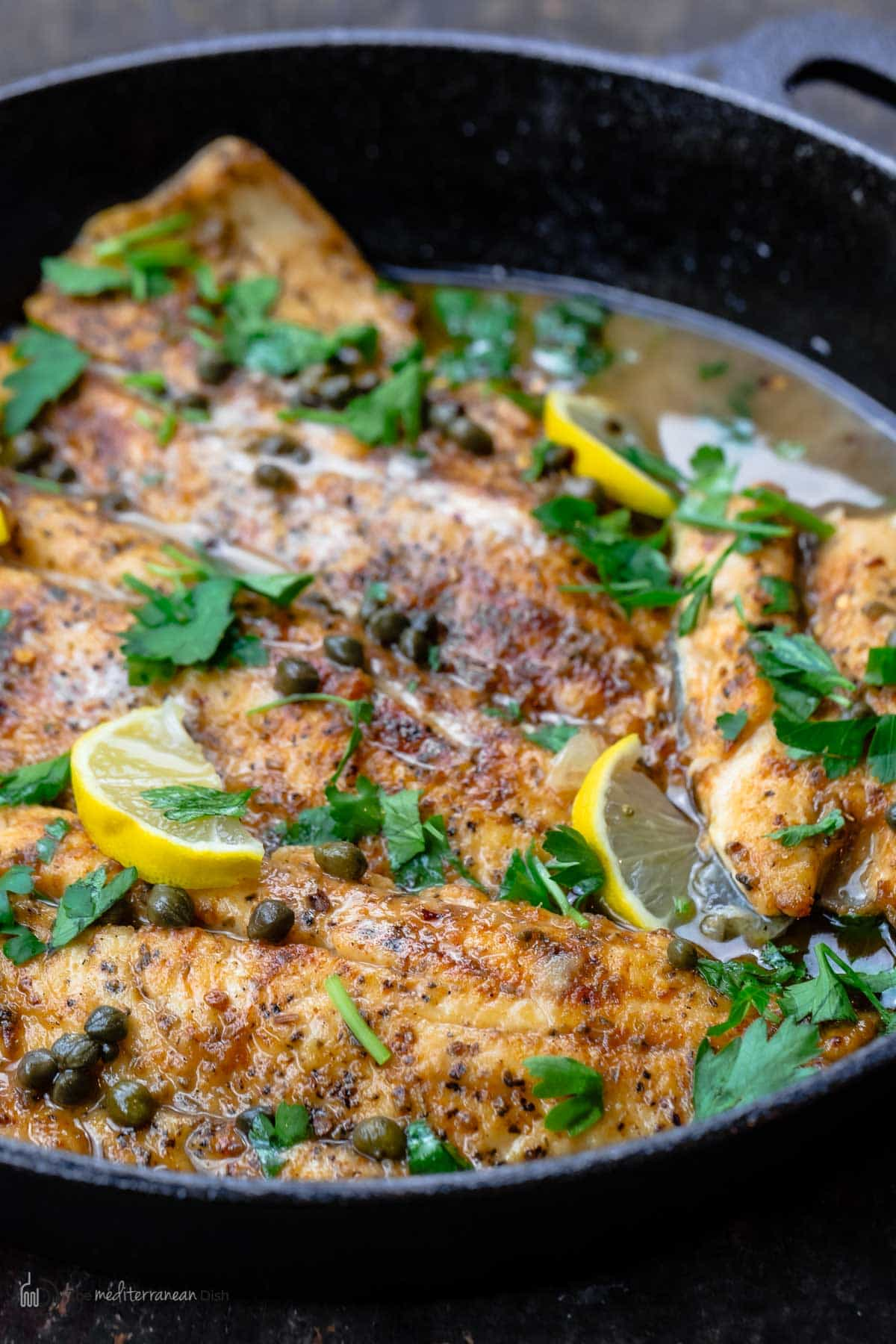 A skillet of fish piccata topped with parsley