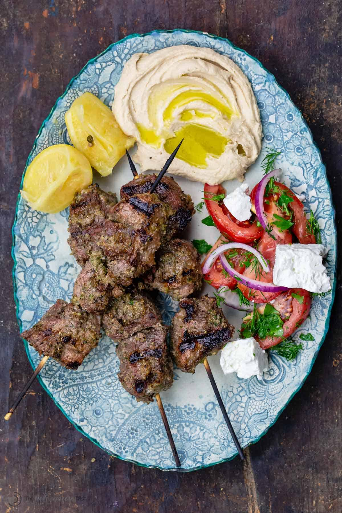 Lamb kabobs served on a plate with veggies and hummus