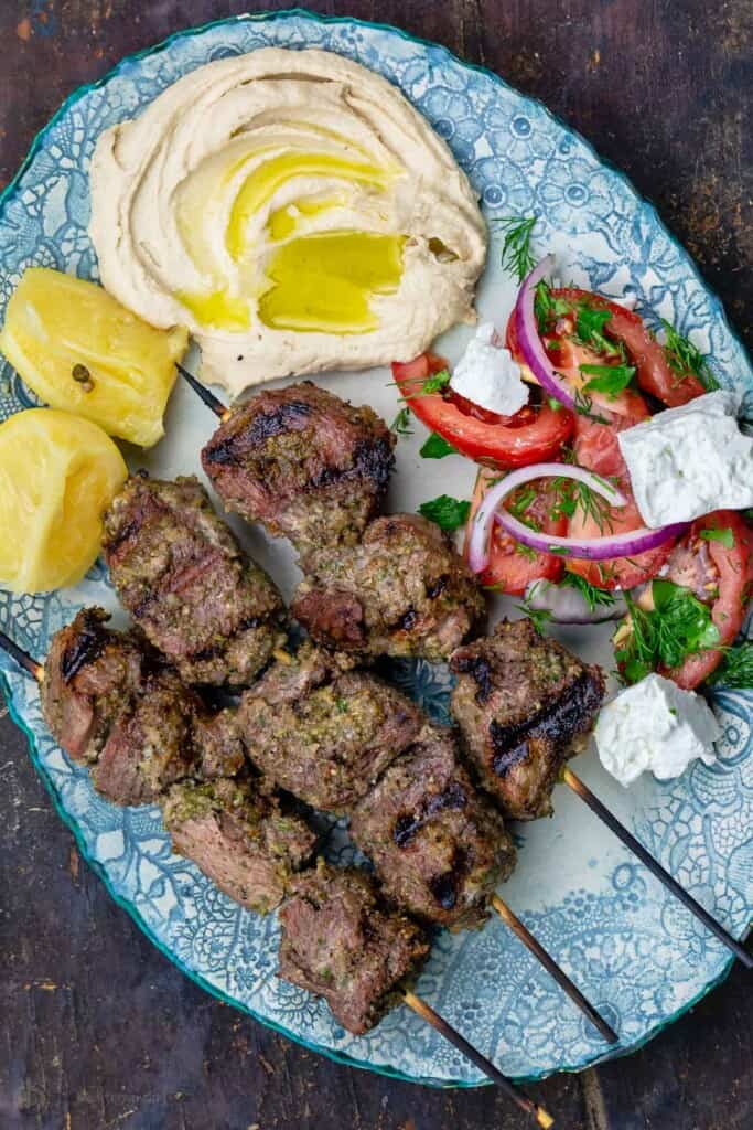 Lamb kabobs served on a plate with a tomato salad and hummus