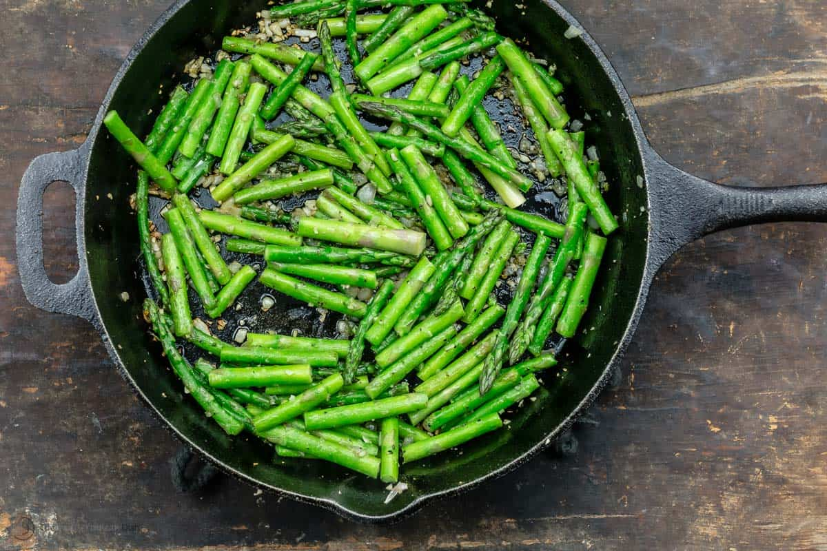 Fresh asparagus cut into 3 inch pieces in a black skillet