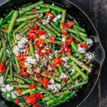 Sauteed asparagus topped with feta and roasted red peppers in a cast iron skillet