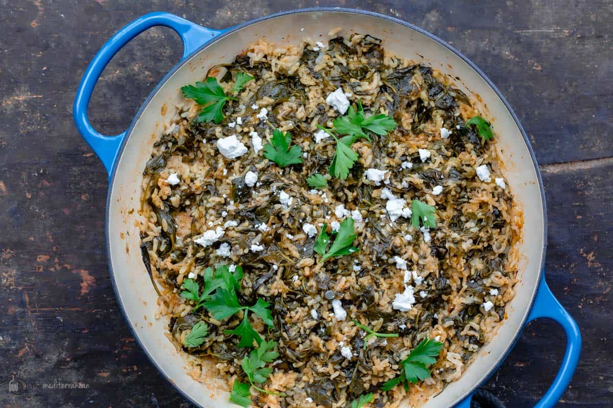 Spanakorizo in a pan topped with feta and parsley