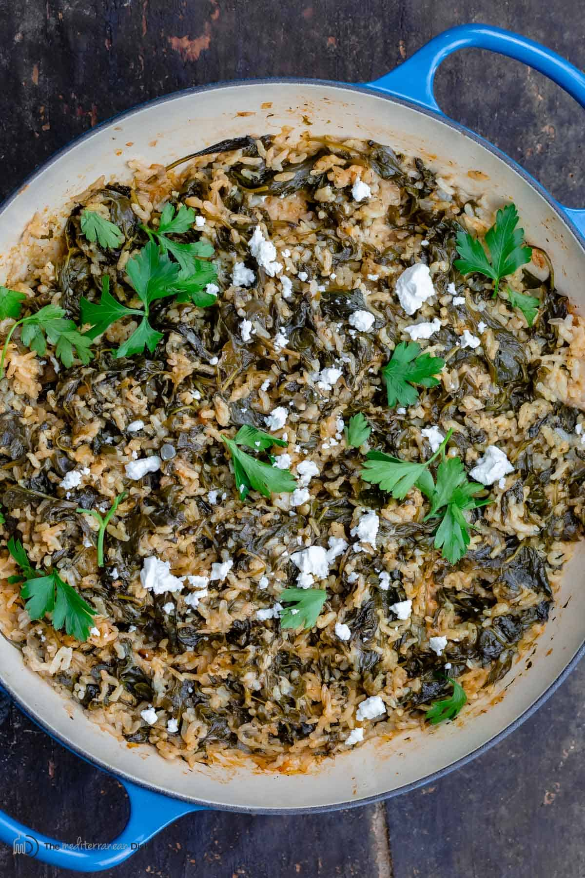 Greek spinach rice topped with feta and parsley in a pan