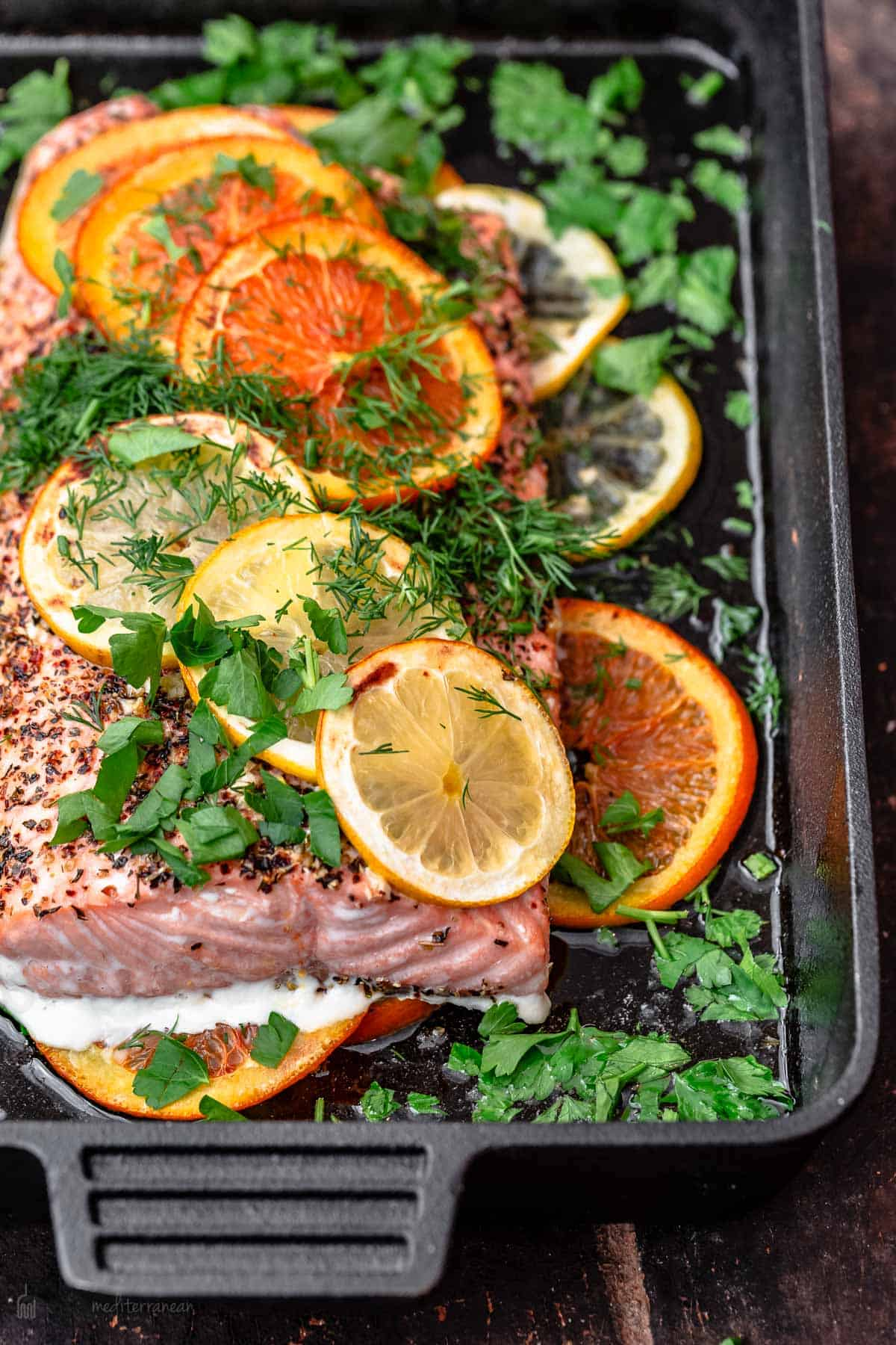 Salmon in cast iron skillet with slices of oranges