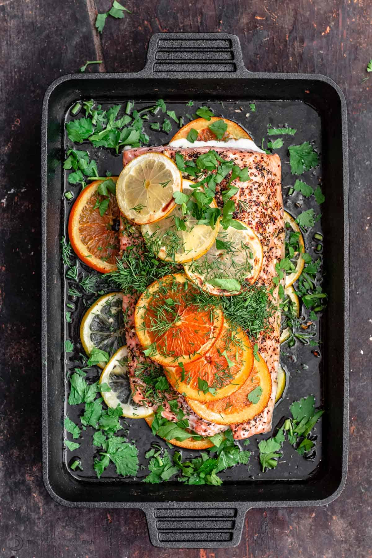Fillet of salmon in skillet with slices of oranges and lemons
