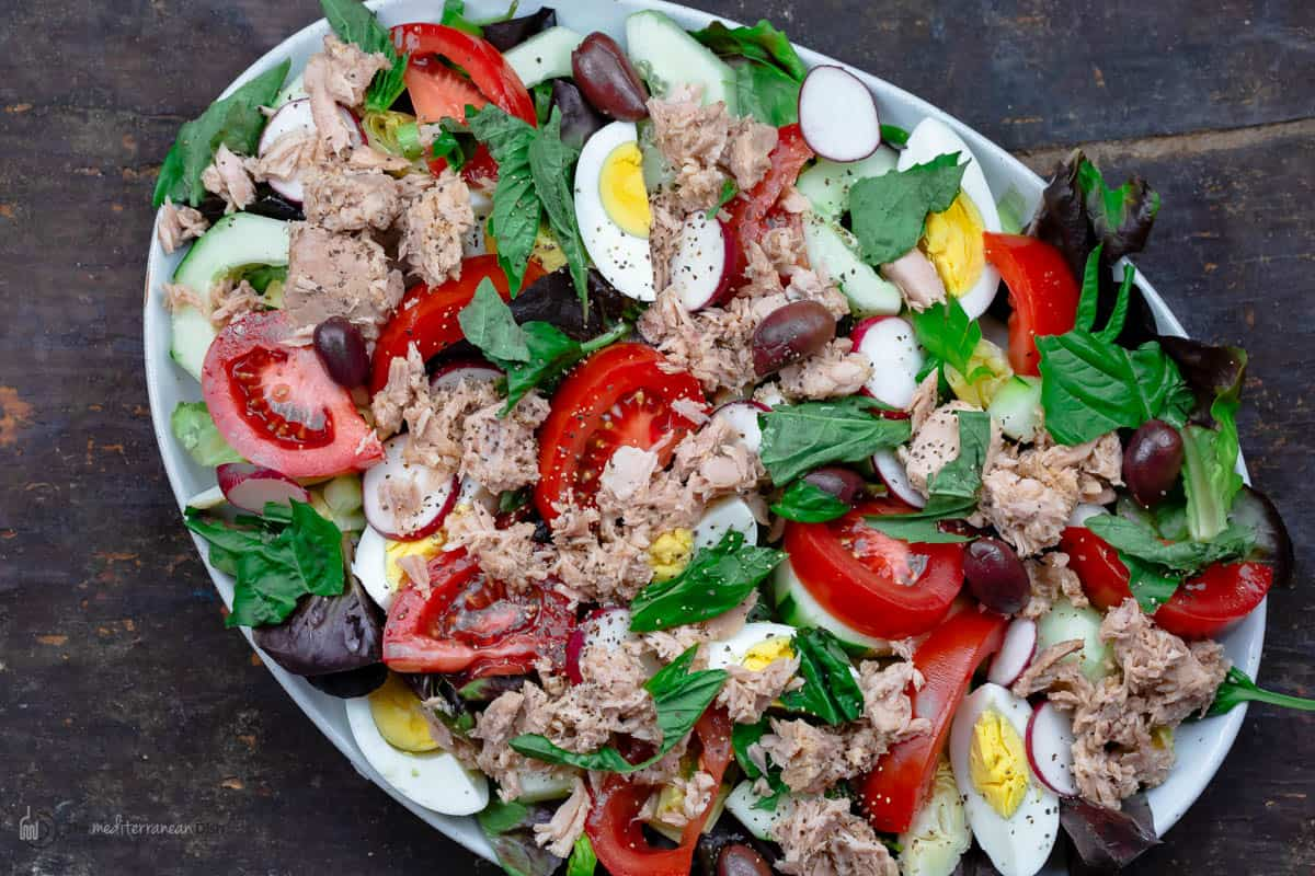 A Bird's-Eye View of Nicoise Salad on a Plate with Olives, Tuna, Lettuce and Boiled Eggs.