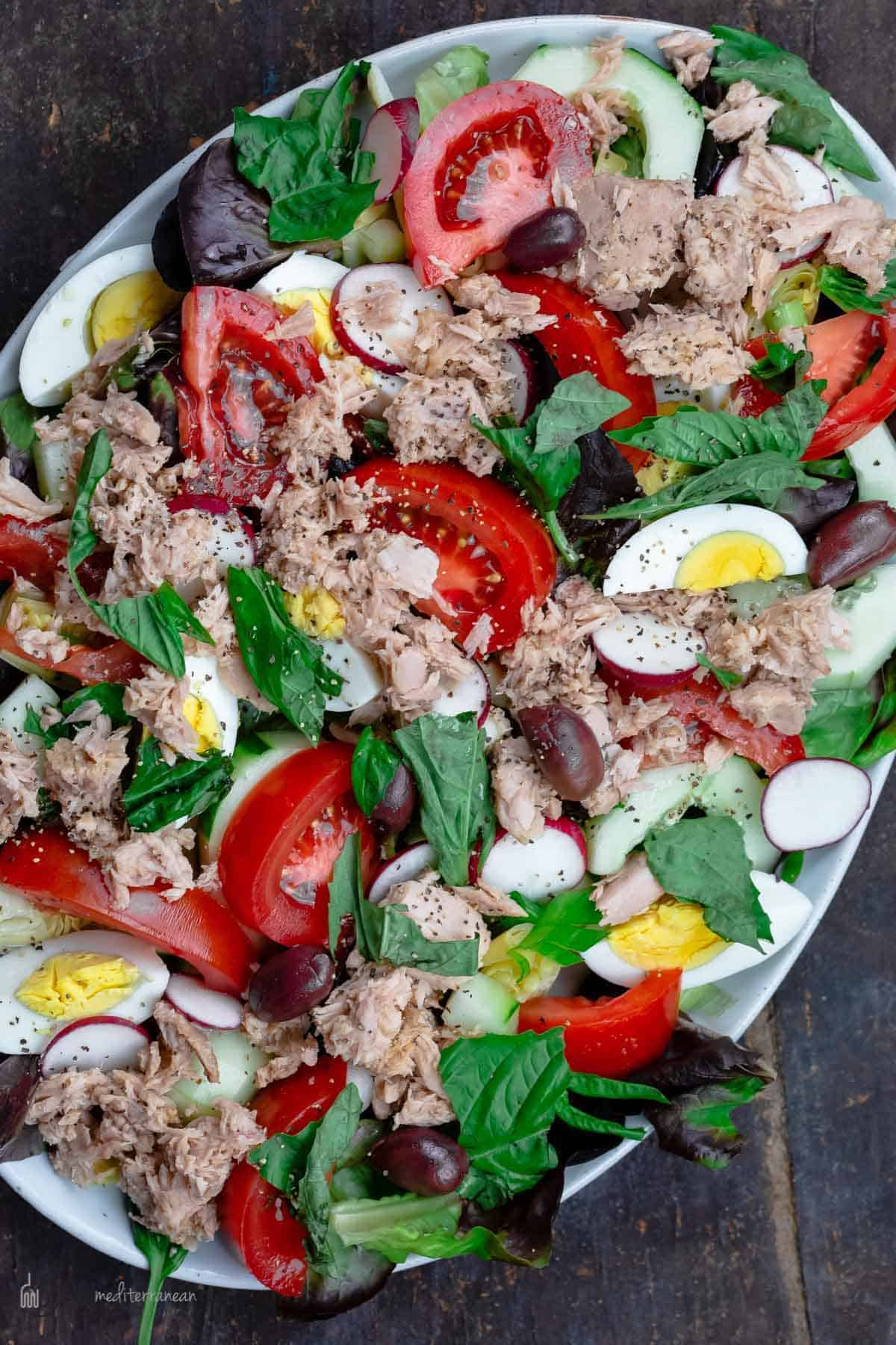 A Nicoise Tuna Salad on a Silver Platter on Top of a Picnic Table