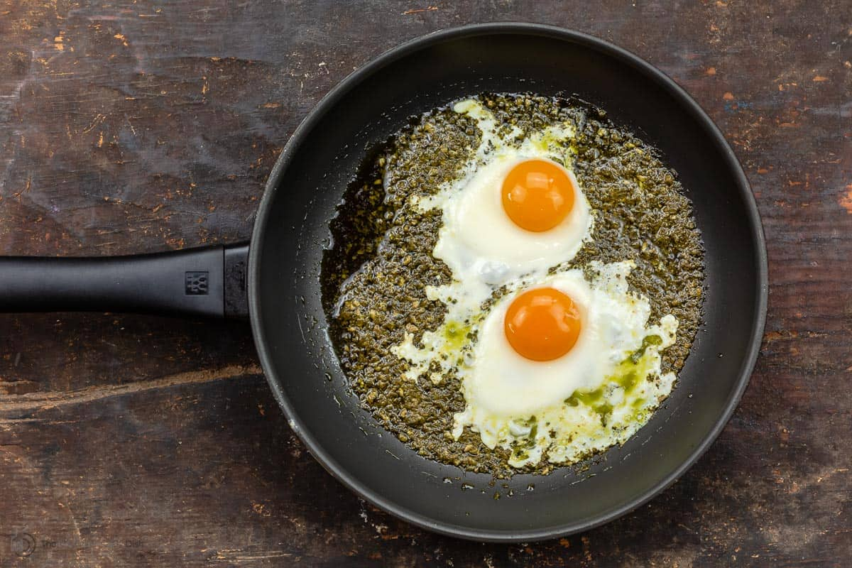 Two sunny side eggs in frying pan with pesto sauce