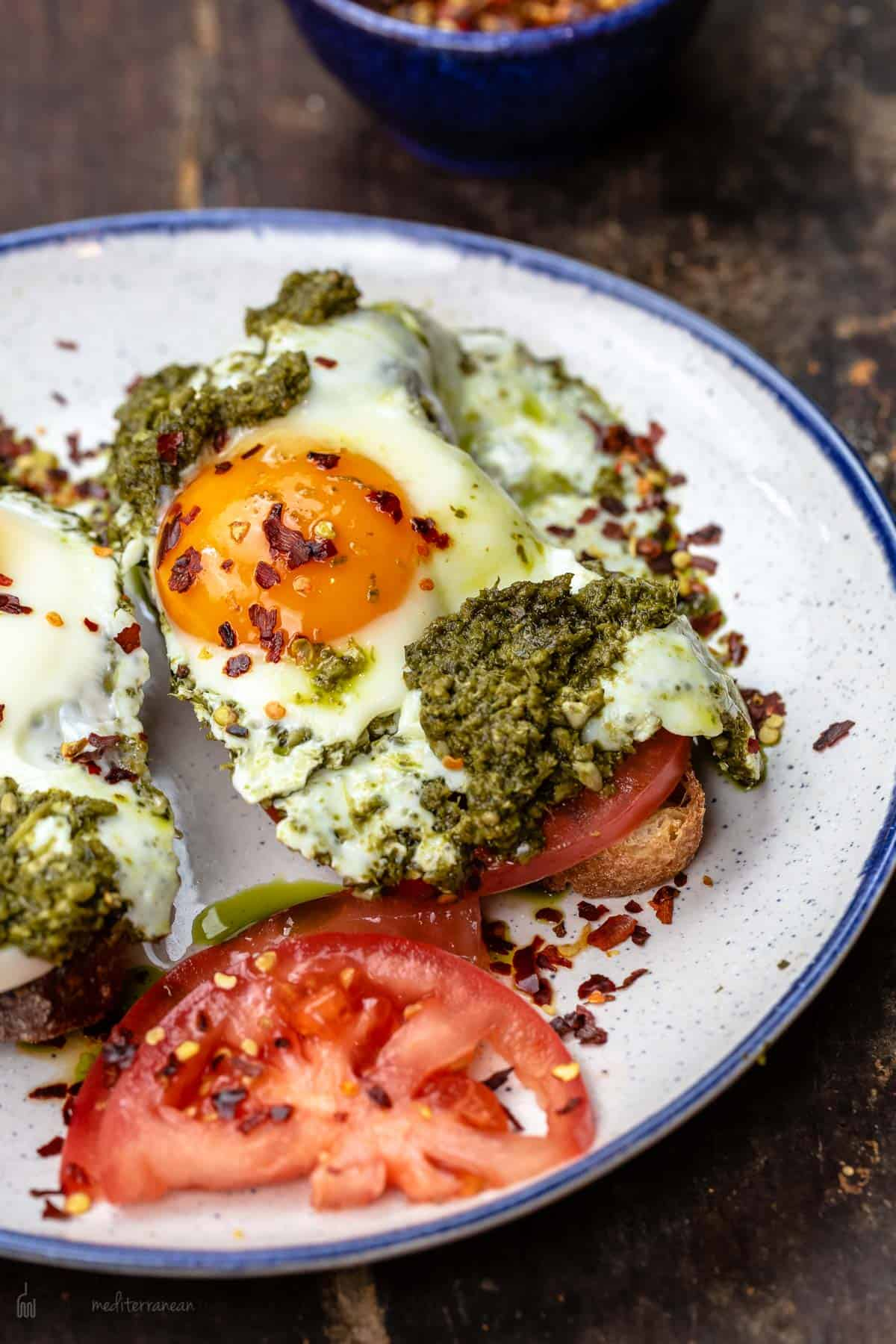 Eggs cooked sunny side with pesto served on a plate
