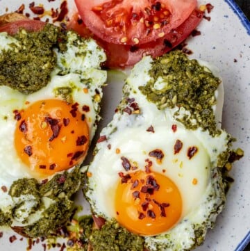 Pesto eggs served on a plate with tomato slices