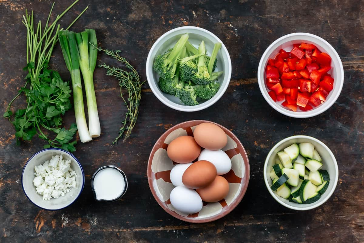 ingredients. Seven Eggs, A Bowl of Diced Red Bell Pepper and the Remaining Frittata Ingredients on a Dark Wooden Surface