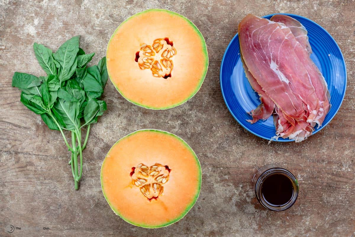 Ingredients including prosciutto, cantaloupe, honey, and basil