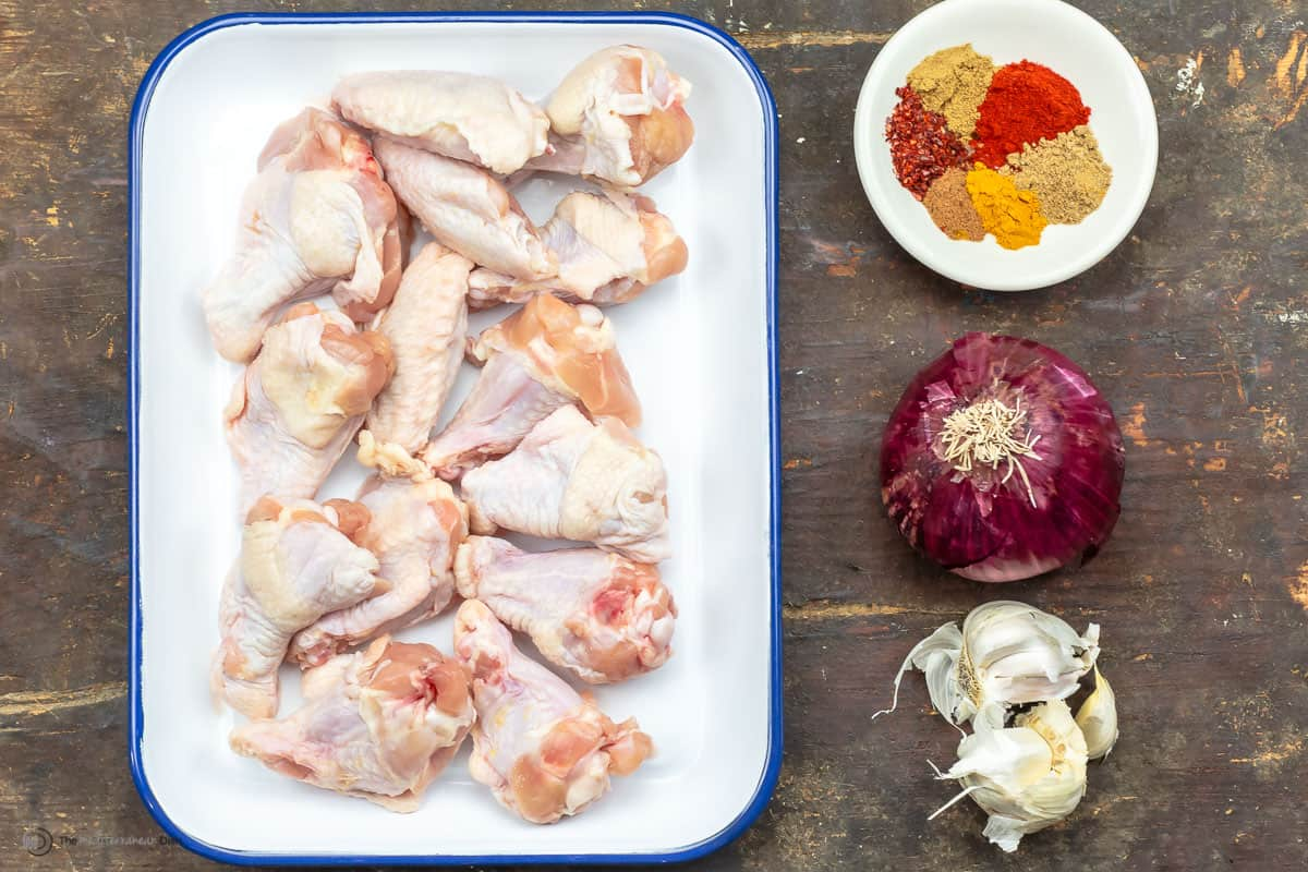 Raw chicken wings on a tray with a dish of spices, an onion and garlic cloves