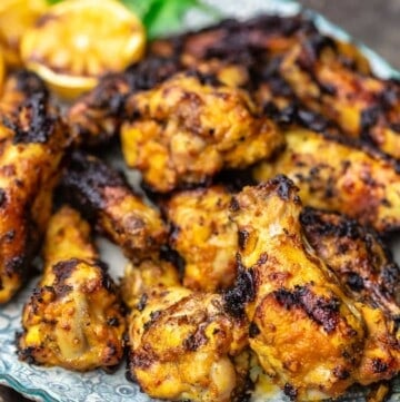 Grilled chicken wings piled on a plate
