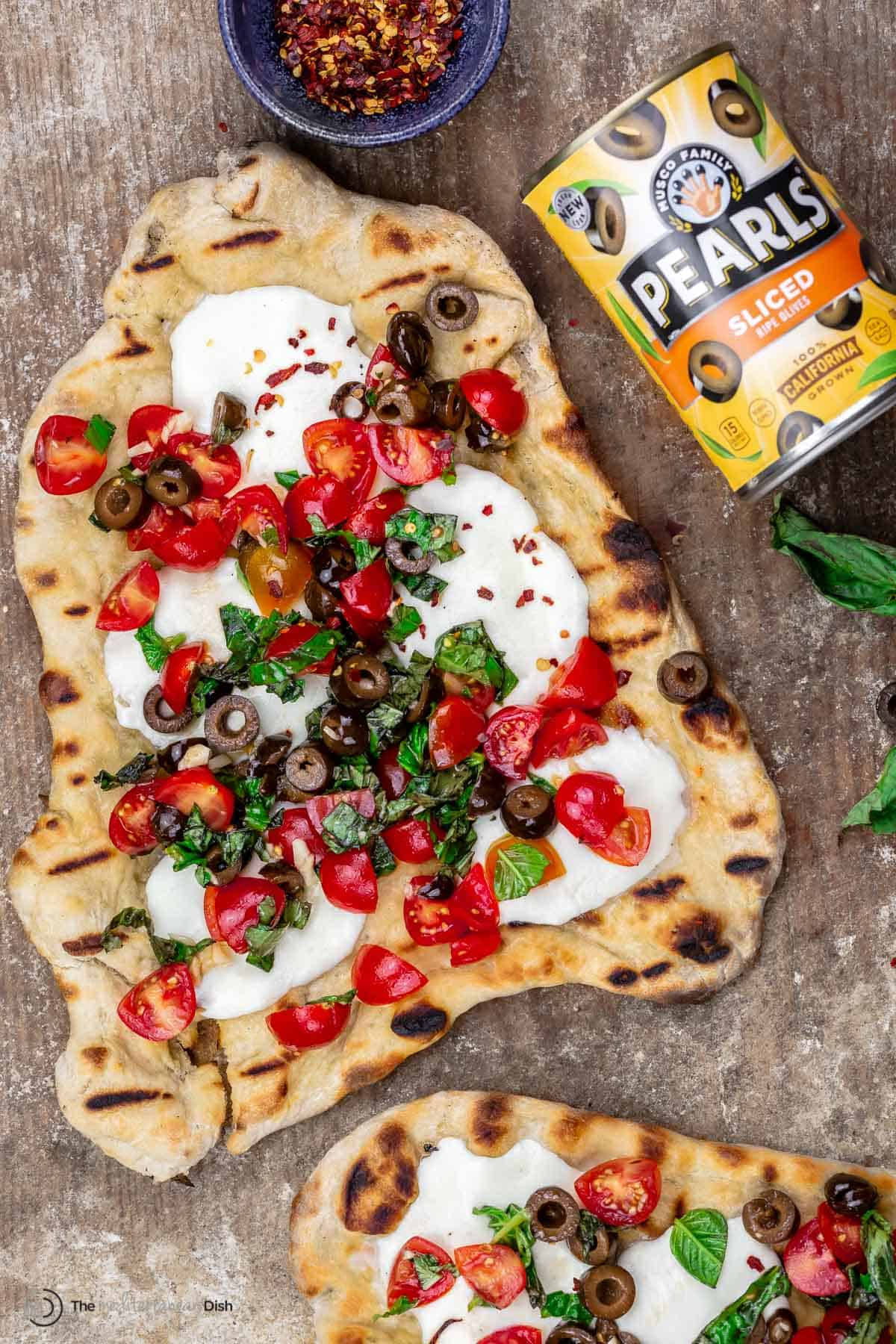 grilled pizza on wood board with a side of red pepper flakes and a can of Pearls Olives