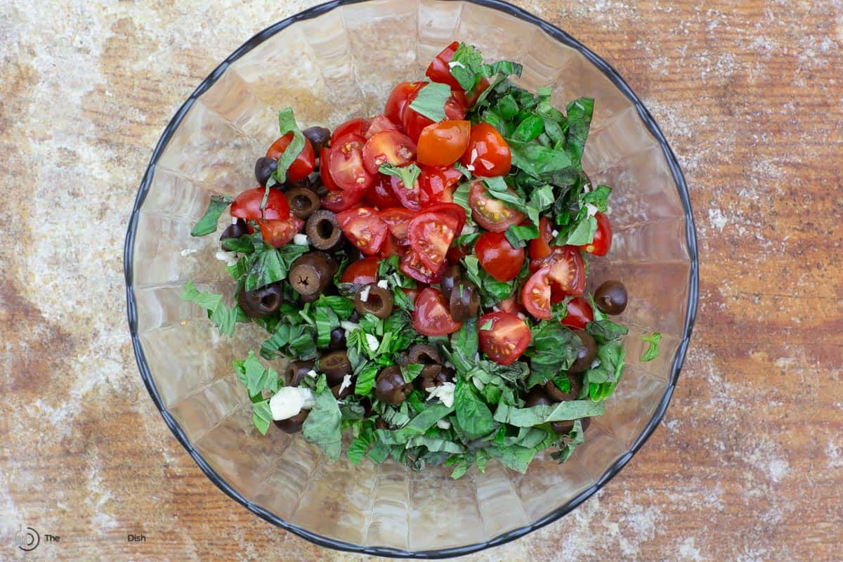olives, tomatoes, basil, and garlic tossed in a bowl