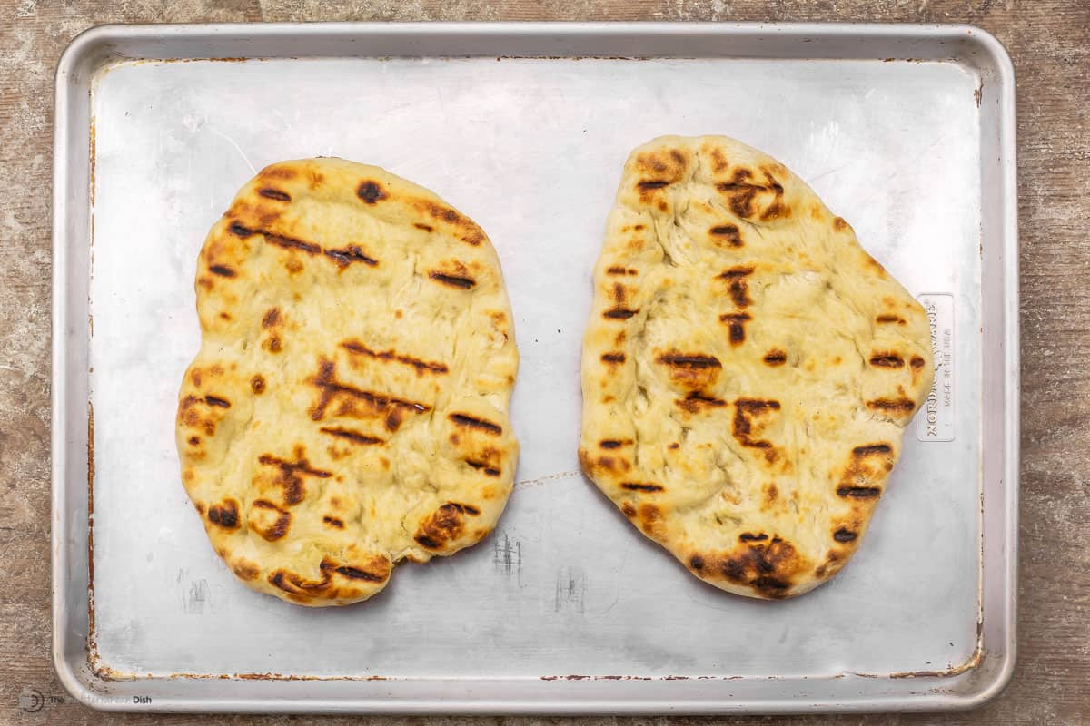 Two grilled pizza crusts on baking sheet