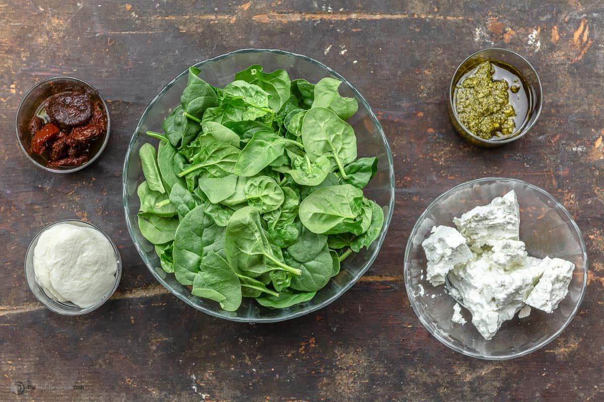 ingredients. Mozzarella, feta, spinach, sun-dried tomatoes, basil pesto