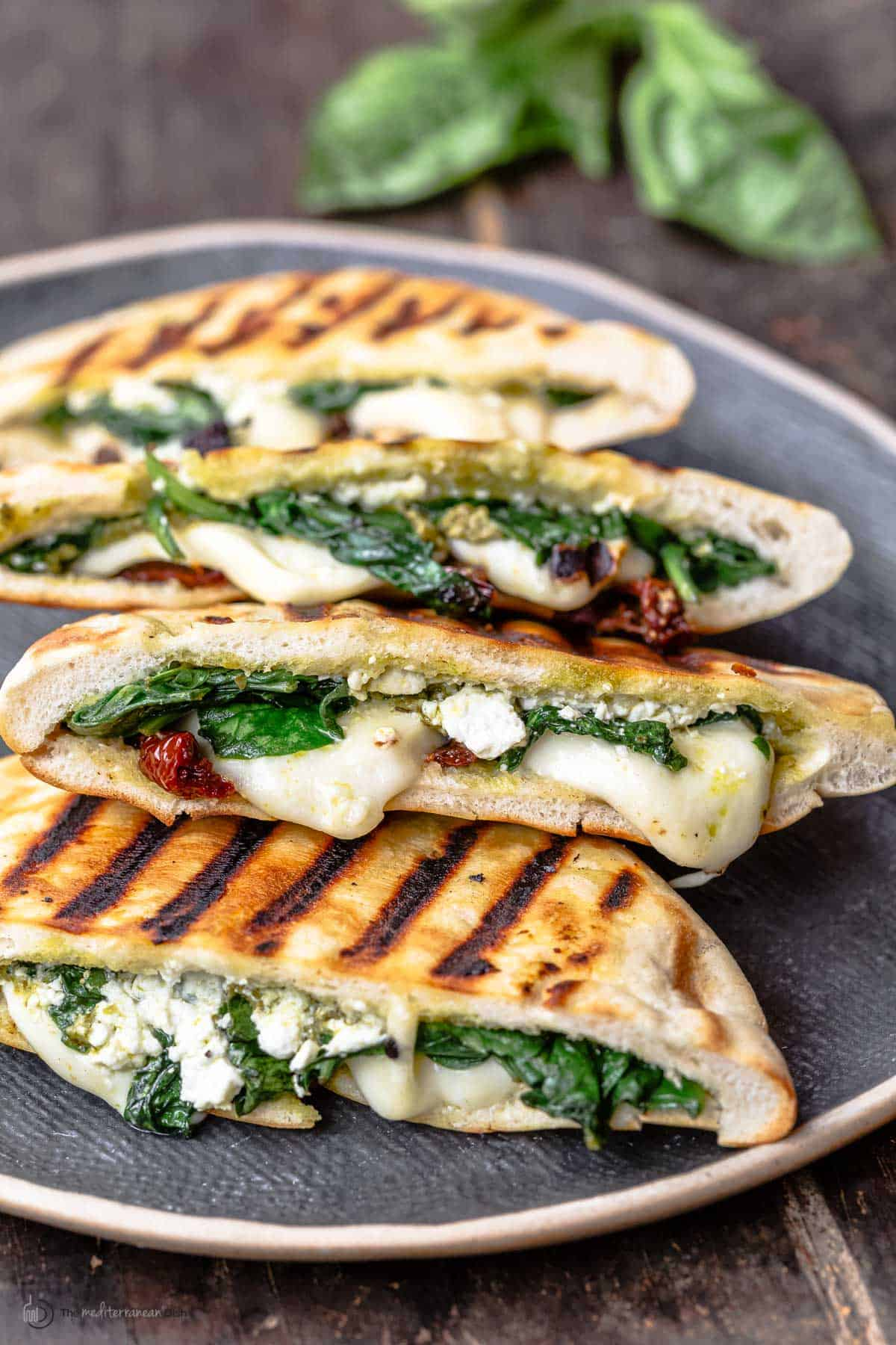 pita grilled cheese sandwiches with melted mozzarella, feta, spinach and sundried tomatoes on a platter