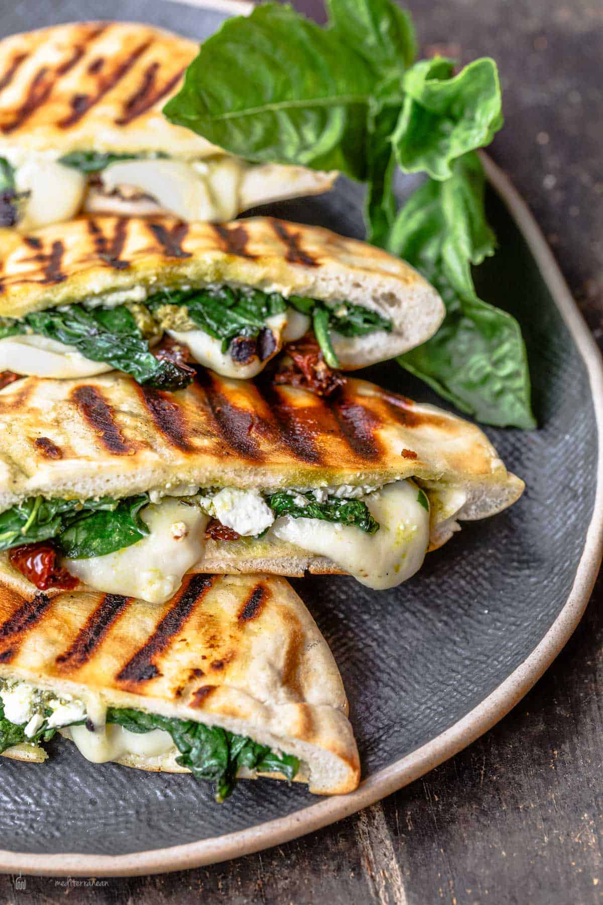 pita grilled cheese sandwiches assembled on black platter with basil garnish