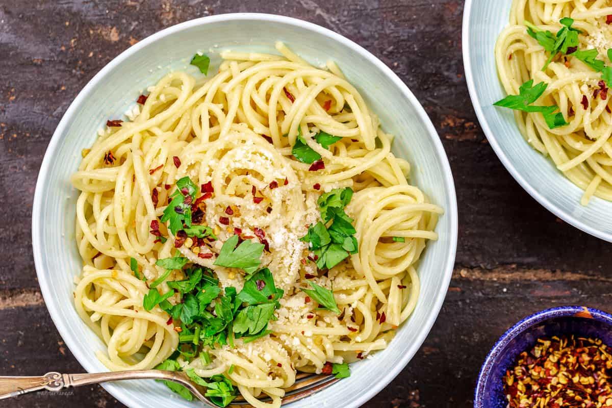 A white bowl of spaghetti aglio e olio